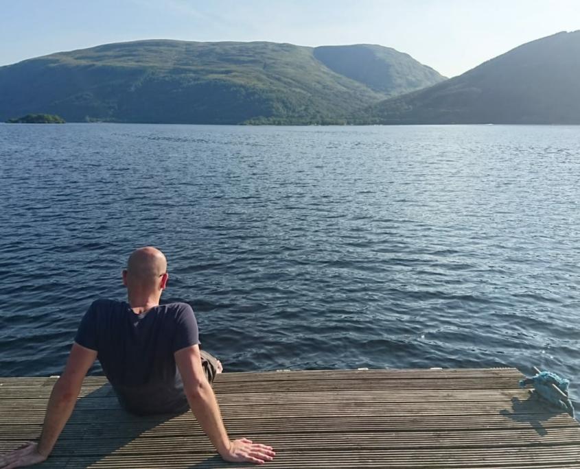 Dr. Volker Rhode sitzt am Wasser und schaut auf Berge