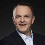 Andreas Holzer lächelt vor schwarzem Hintergrund