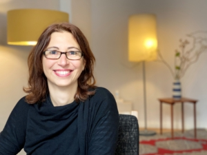 Petra Markus lächelt sitzend in einem Raum